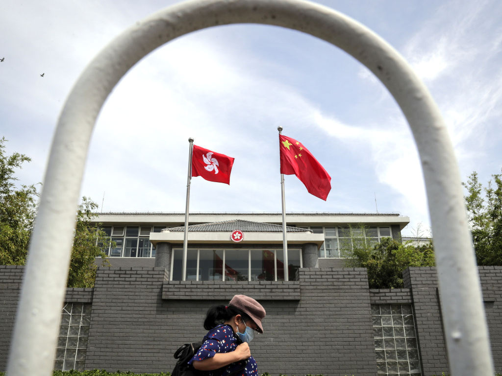 A woman wearing a protective face mask walks by the Government of Hong Kong Special Administrative Region office building in Beijing in June following the imposition of a national security law on Hong Kong. Ten Hong Kong fugitives were sentenced to prison Wednesday for illegally crossing international boundaries.
