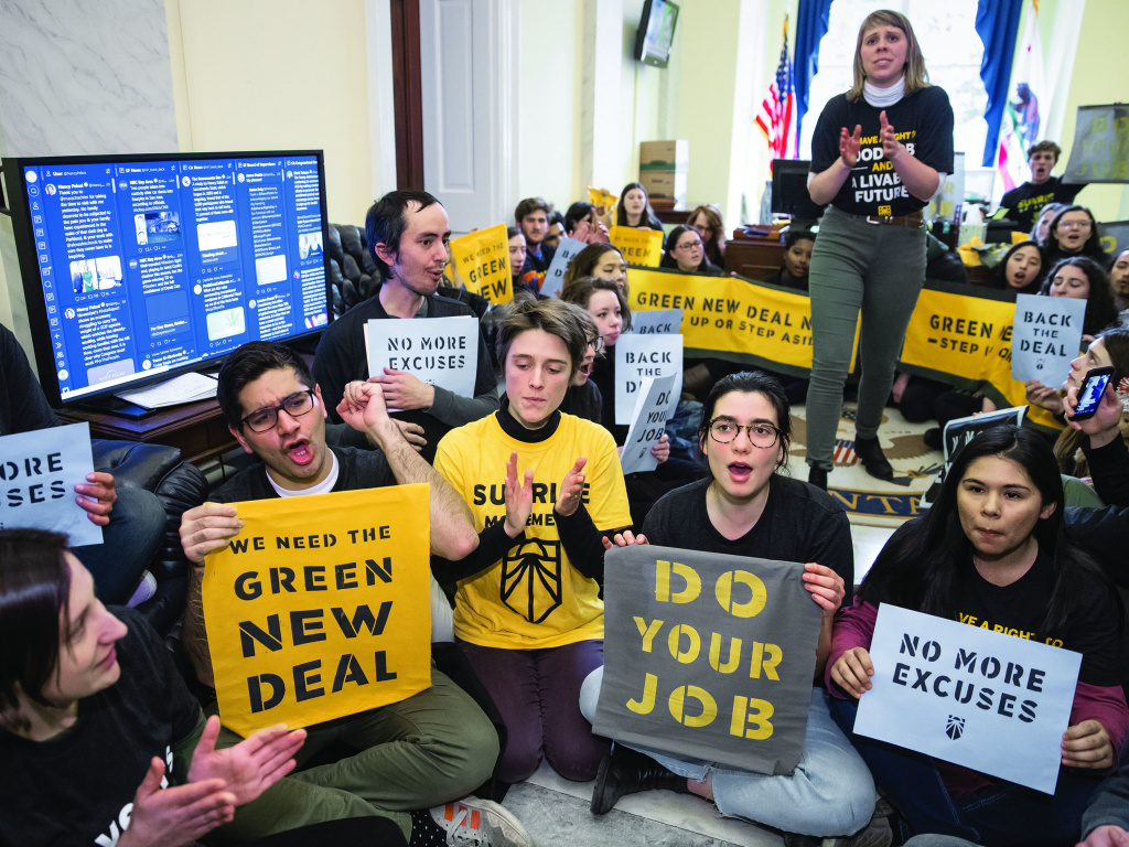 Environmental activists occupy the office of House Democratic Leader Nancy Pelosi this past December. They plan more sit-ins to push for support of a sweeping resolution to address climate change.