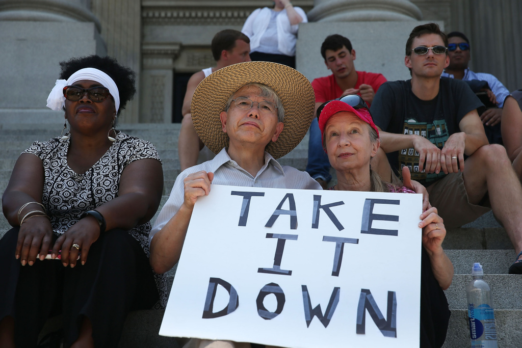 Gwen Alston, Kuniharu kubodera and Barbara Kubodera (L-R) sit on the steps of the capitol as they show their support for the removal of the confederate flag from the Capitol grounds, during a protest in support of the flags removal on June 23, 2015 in Columbia, South Carolina.