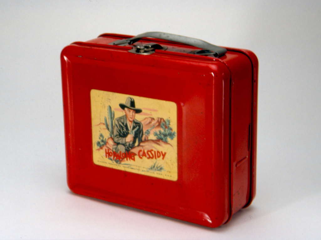 This steel lunch box, made by Aladdin Industries in 1950, was the first to bear a licensed image, and helped Aladdin launch a new product line that would last for decades. Hopalong Cassidy was a popular TV, radio and comic series.