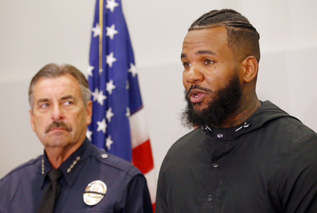 Los Angeles Police Chief Charlie Beck, left, listens as rapper The Game speaks at a news conference following a meeting he and fellow rapper Snoop Dogg had with Beck and Mayor Eric Garcetti at police headquarters in Los Angeles Friday, July 8, 2016. The rappers led a peaceful march where they urged improved relations between police and minority communities in the wake of shootings in Dallas that left five police officers dead.