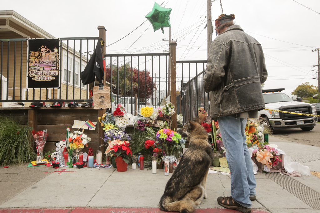 A man looks at a makeshift memorial near the site of a warehouse fire that has claimed the lives of at least thirty-six people on December 5, 2016 in Oakland, California. The fire took place during a musical event late Friday night.