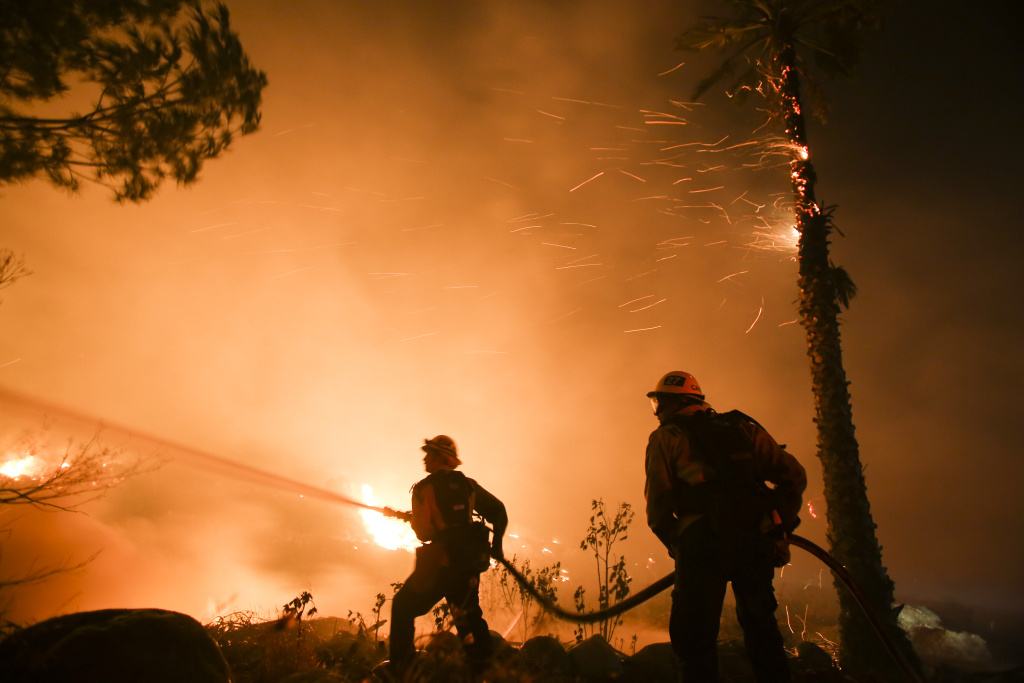 Firefighters battle a wildfire as it burns along a hillside near homes in Santa Paula, California, on December 5, 2017.