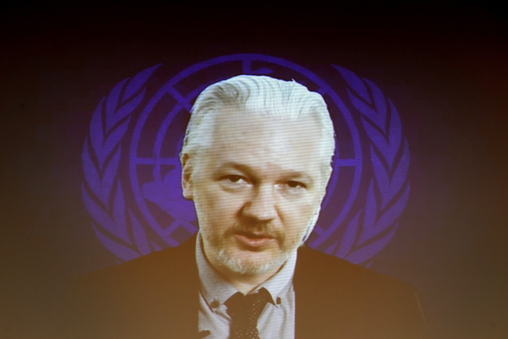 WikiLeaks founder Julian Assange is seen on a screen speaking via web cast from the Ecuadorian Embassy in London during an event on the sideline of the United Nations (UN) Human Rights Council session on March 23, 2015 in Geneva.