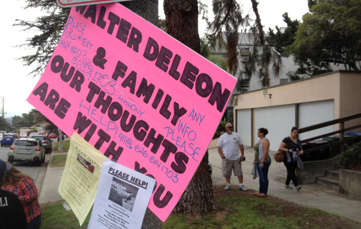 A man hold a sign and waves a rag in support of Walter DeLeon, who was unarmed when an LAPD officer shot and critically wounded him June 19.