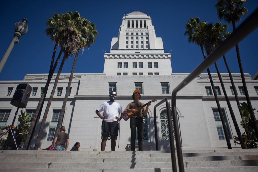 Occupy Los Angeles protesters look at cyclist streaming past from their vantage point on the steps of City Hall.