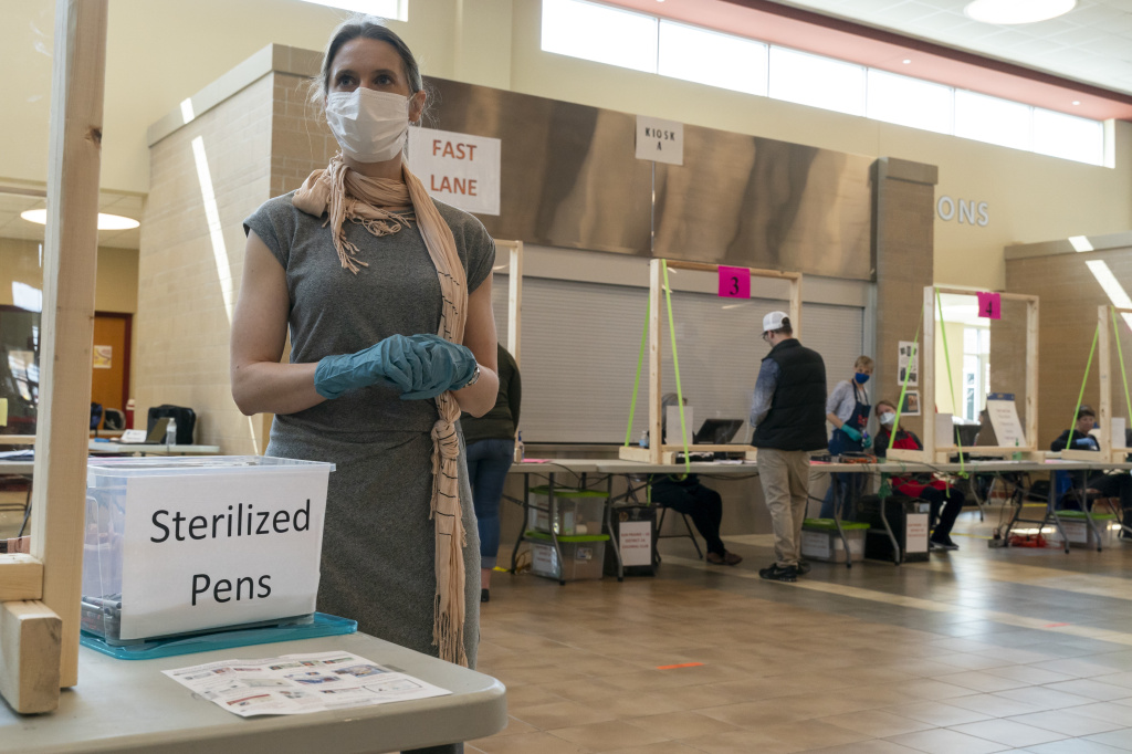 A poll worker in Sun Prairie, Wis., is seen during the state's April 7 primary. A record number of Wisconsin voters are expected to vote by mail this fall, but polls indicate Republicans are far more likely to vote in person, which has some GOP officials worried it could hurt the party's chances.