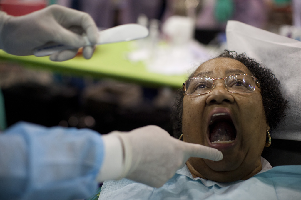Dr. Paul Schafer begins to make a mold for patient Ida Franklin during a free health clinic at the L.A. Sports Arena. Despite greater access to health insurance through the Affordable Care Act, the program will see 1,000 each day over the four-day event.