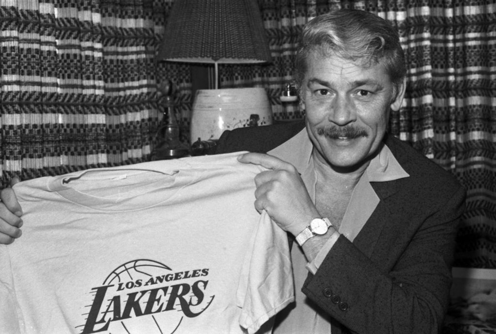 In this June 18, 1981 file photo, Jerry Buss holds a Los Angeles Lakers shirt in Los Angeles. Buss, the Lakers' playboy owner who shepherded the NBA franchise to 10 championships, has died. He was 79.