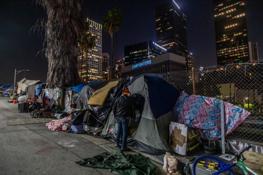 Robert King Geiser, 35 years-old, after 2 years living on the street, stands outside his tent next to the 110 Freeway, during the novel Coronavirus, COVID-19, pandemic in Los Angeles California on May 25, 2020.