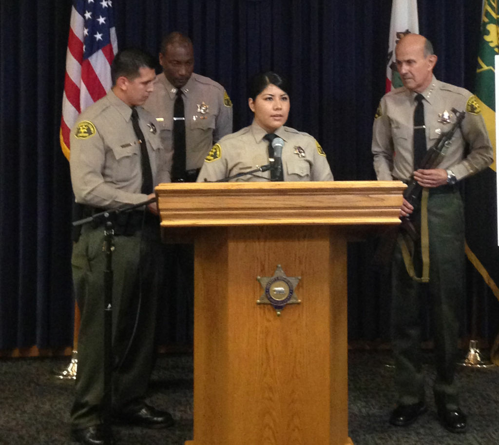 L.A. Sheriff Lee Baca (far right) stands with two sheriff's deputies who were shot at with an AK-47 (similar to the one in Baca's hands) on January 8 in Lynwood.