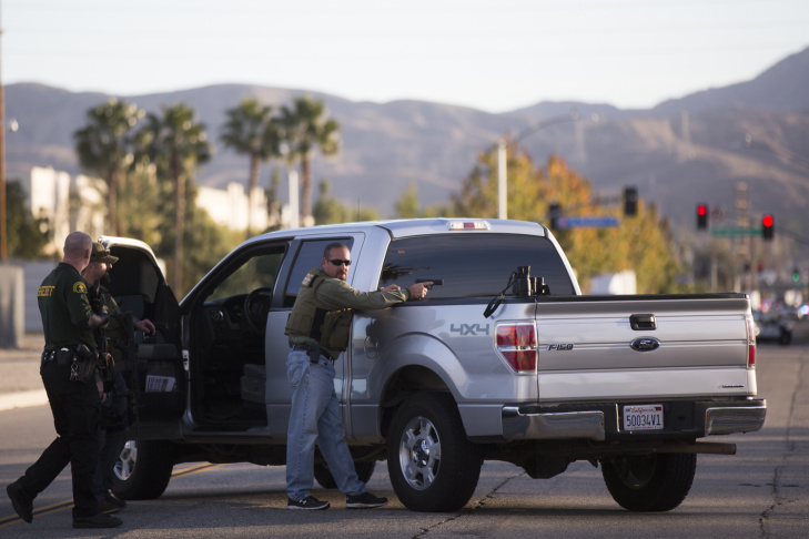 Redlands Police stand near Center Street and Pine Avenue on Wednesday night, Dec. 2, 2015 as authorities serve a search warrant following a mass shooting inside the the Inland Regional Center in San Bernardino on Wednesday, Dec. 2, 2015.
