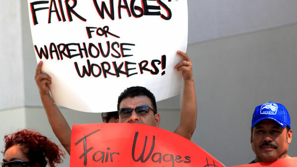 Warehouse workers rally in Riverside after announcing a class action lawsuit against a Wal-Mart warehouse operated by Schneider Logistics.