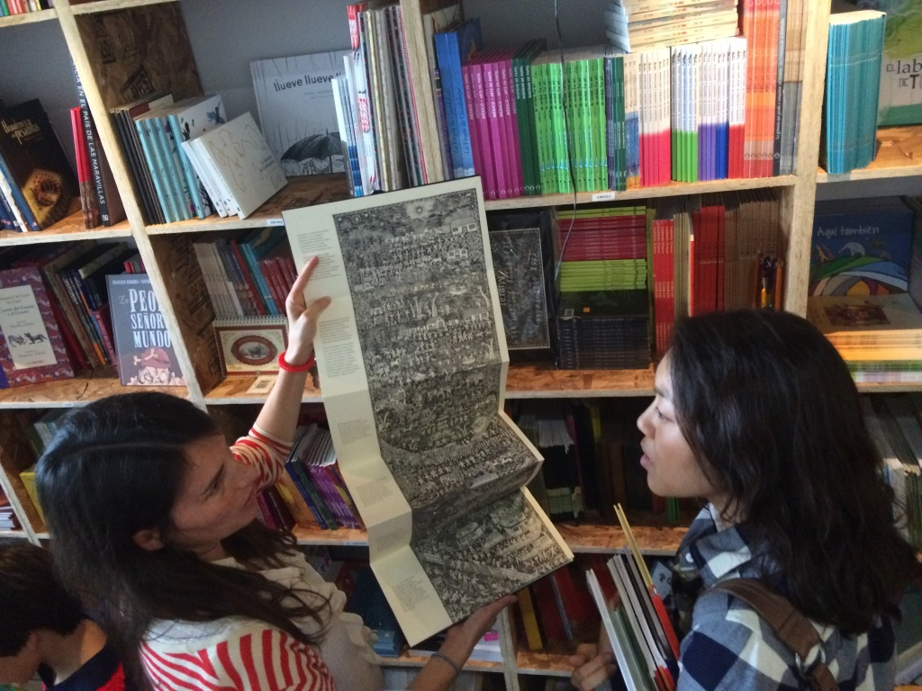 La Librería co-founder, Chiara Arroyo (left) shows a customer the children's book from Mexico called