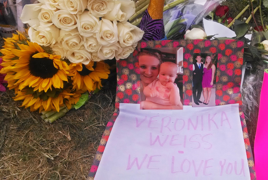 Flowers, photos and a note adorn a sidewalk memorial for victims of a May 23, 2014 shooting rampage in Isla Vista.