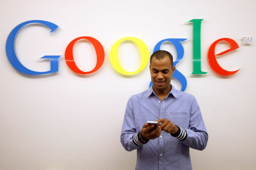 A visitor uses a cell phone in front of the Google logo. The search giant isn't operating a search monopoly, according to the Federal Trade Commission.