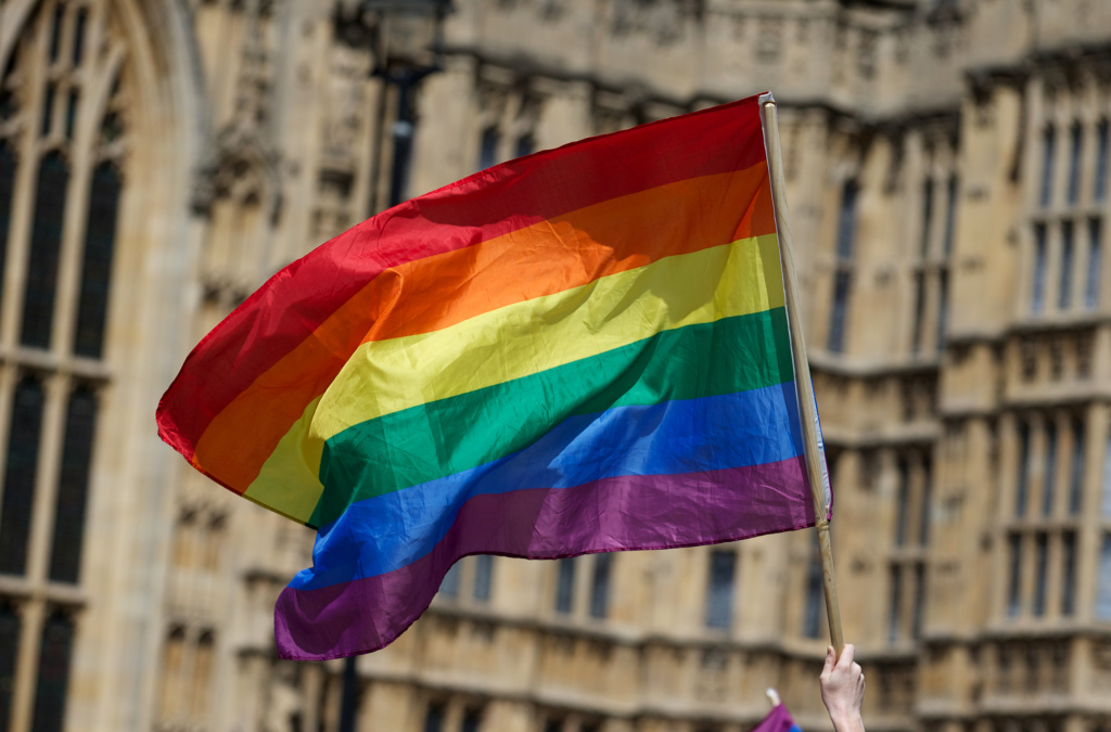 File: A gay campaigner waves the rainbow flag during a rally outside the Houses of Parliament as the Marriage (Same Sex Couples) Bill gets an unopposed third reading by the Lords in central London on July 15, 2013.