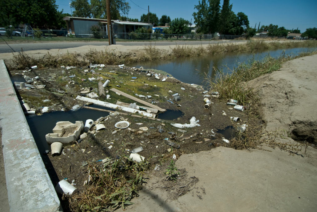 Garbage collects in an irrigation ditch that runs through Matheny Tract, where residents' tapwater flows from a single well with arsenic levels that exceed federal limits.