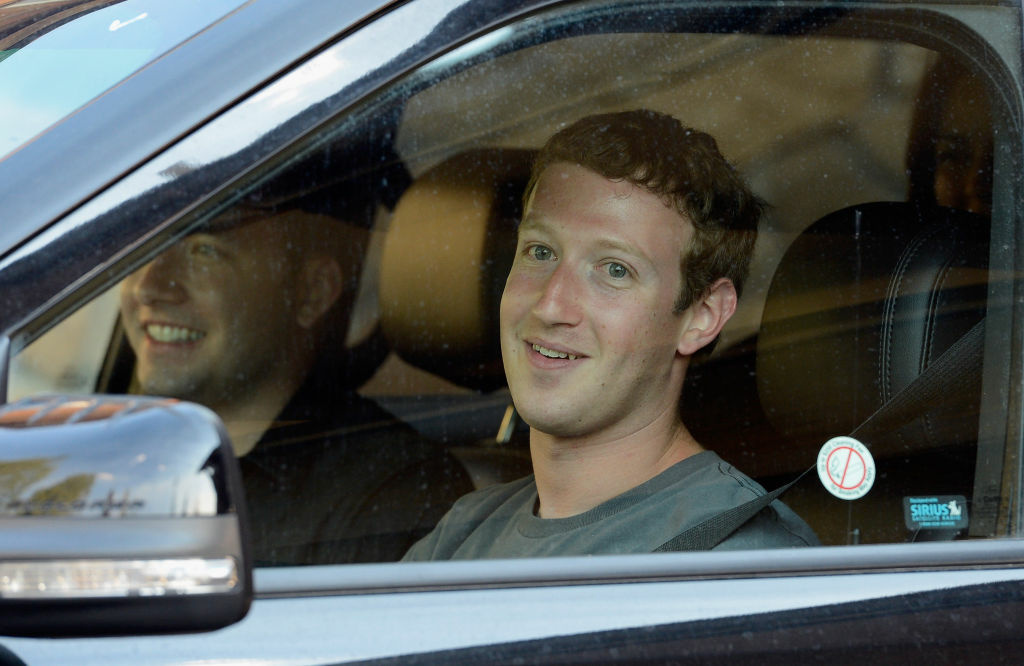 Mark Zuckerberg, chief executive officer and founder of Facebook Inc., right, and Andrew 'Drew' Houston, founder and chief executive of Dropbox, wait in a parked car for the traffic to clear out at the Sun Valley Lodge during the Allen & Company Sun Valley Conference on July 12, 2012, in Sun Valley, Idaho. The conference has been hosted annually by the investment firm Allen & Company each July since 1983. The conference is typically attended by many of the world's most powerful media executives.