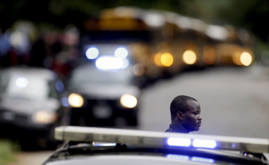 A Dekalb County Police officer stands guard as students from Ronald E. McNair Discovery Learning Academy board school buses to take them to reunite with their parents after they were evacuated after reports of a gunman entered the school, Tuesday, Aug. 20, 2013, in Decatur, Ga. All students and teachers are safe and a suspect is in custody after gunfire was heard at the Atlanta-area elementary school.
