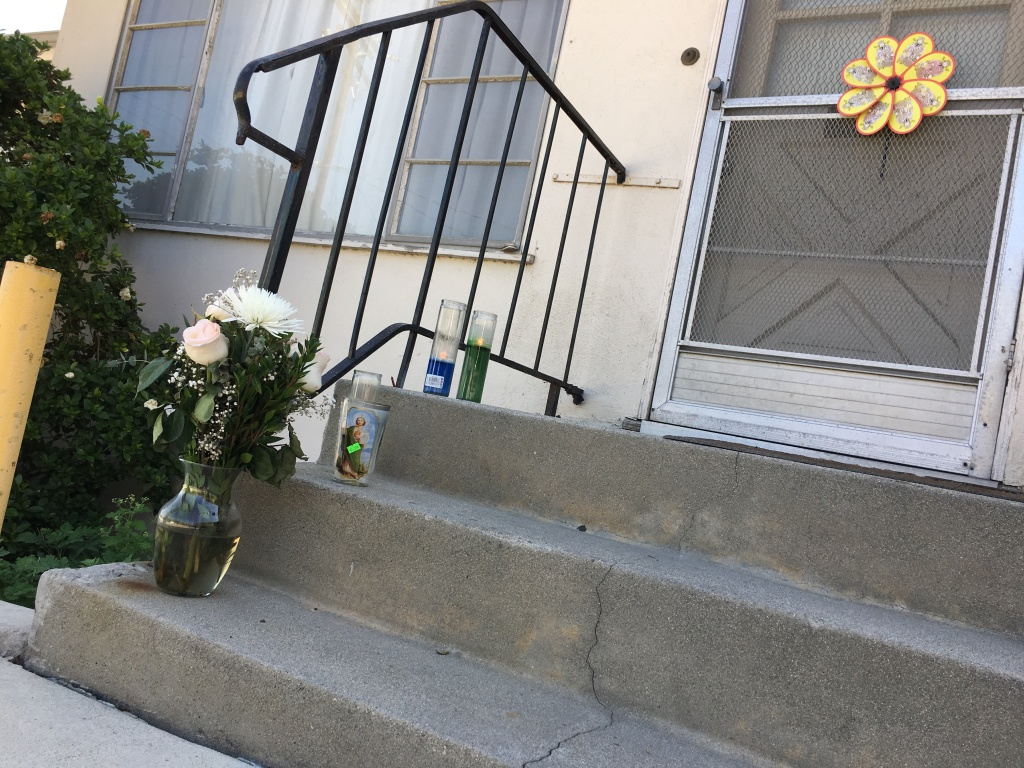A bouquet of white flowers and votive candles had been placed at the doorstep of the home Teodulo Elias Vides, Alhambra apartment on Tuesday..