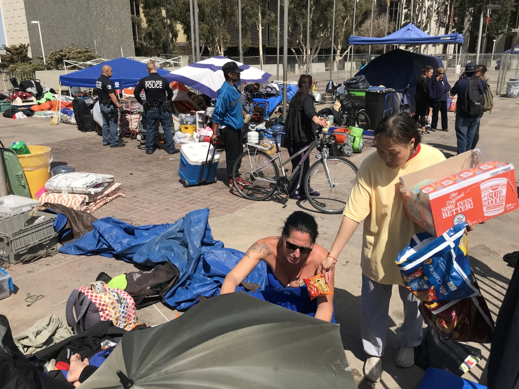 A volunteer hands out food to homeless people leaving the Civic Center homeless encampment on April 12, 2018.