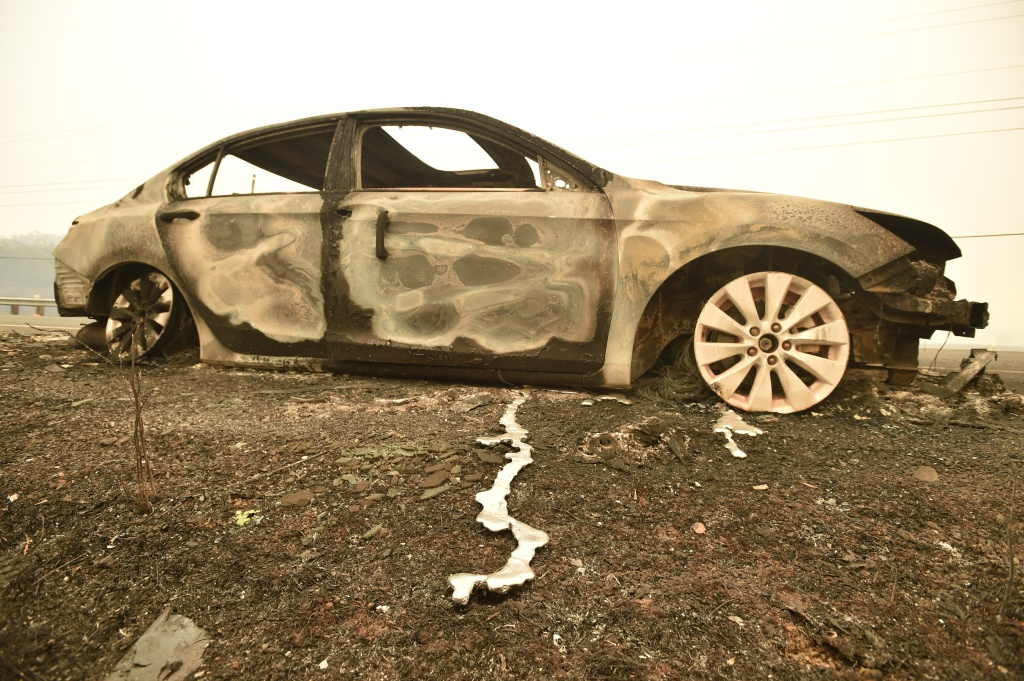 Melted metal flows from a burned out car abandoned on a highway during the Valley Fire in Middletown, California on September 13, 2015. The governor of California declared a state of emergency Sunday as raging wildfires spread in the northern part of the drought-ridden US state, forcing thousands to flee the flames. The town of Middletown, population 1,300, was particularly devastated by the Valley Fire, according to local daily Santa Rosa Press-Democrat, which said the fire grew from 50 acres to 10,000 over just five hours Saturday -- before quadrupling in size overnight.
