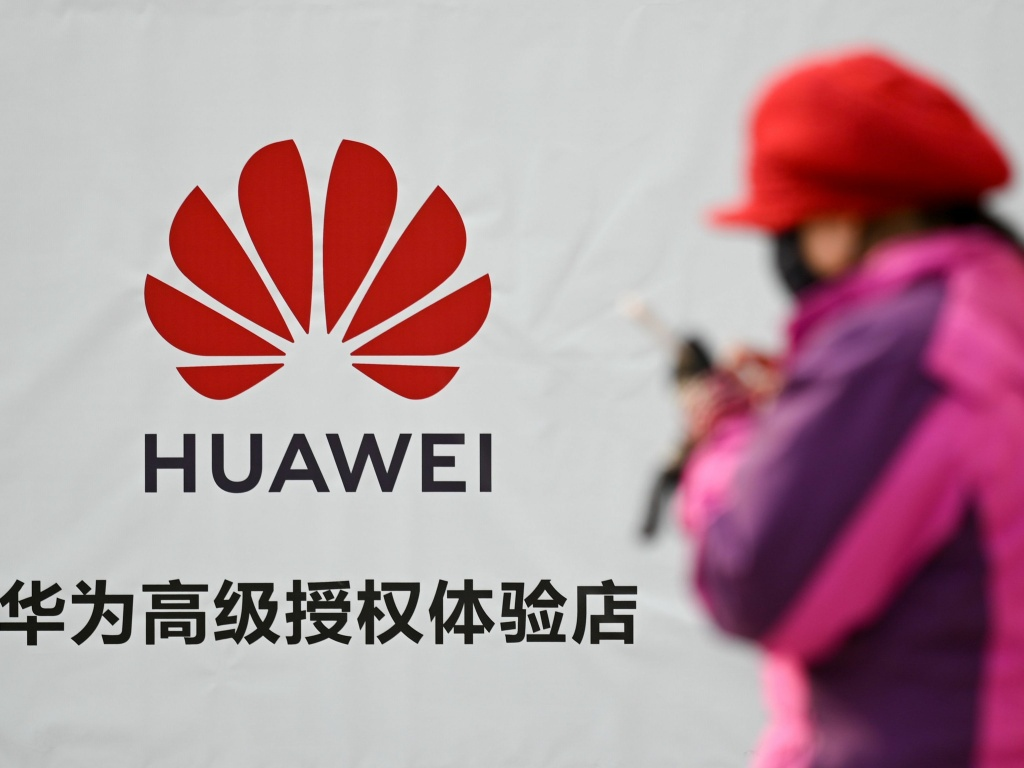 A woman uses her smartphone outside a Huawei store in Beijing