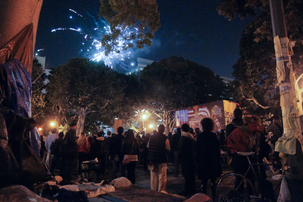 Protesters in the Occupy LA encampment on the south lawn of City Hall watch fireworks shot off from within the camp.