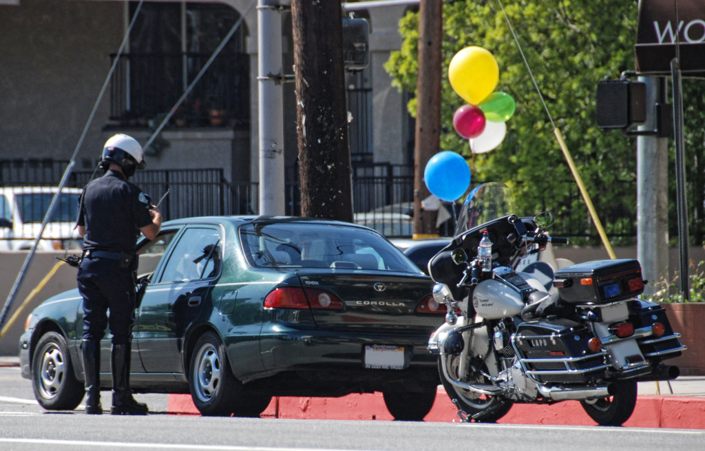 An LAPD motorcycle officer writes a traffic ticket in this file photo. A new lawsuit seeks to stop automatic license suspensions for low-income drivers who have unpaid traffic fines.