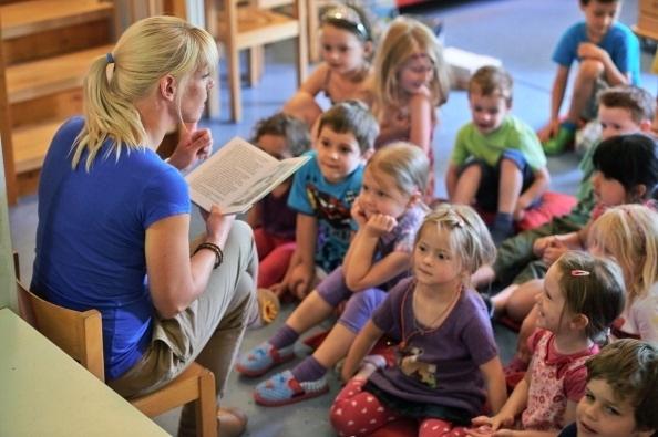 Kindergarten teacher Jennifer Karbot reads a fairy tale about ghosts to her children in a Kindergarten on July 11, 2013 in Pfungstadt, Germany.