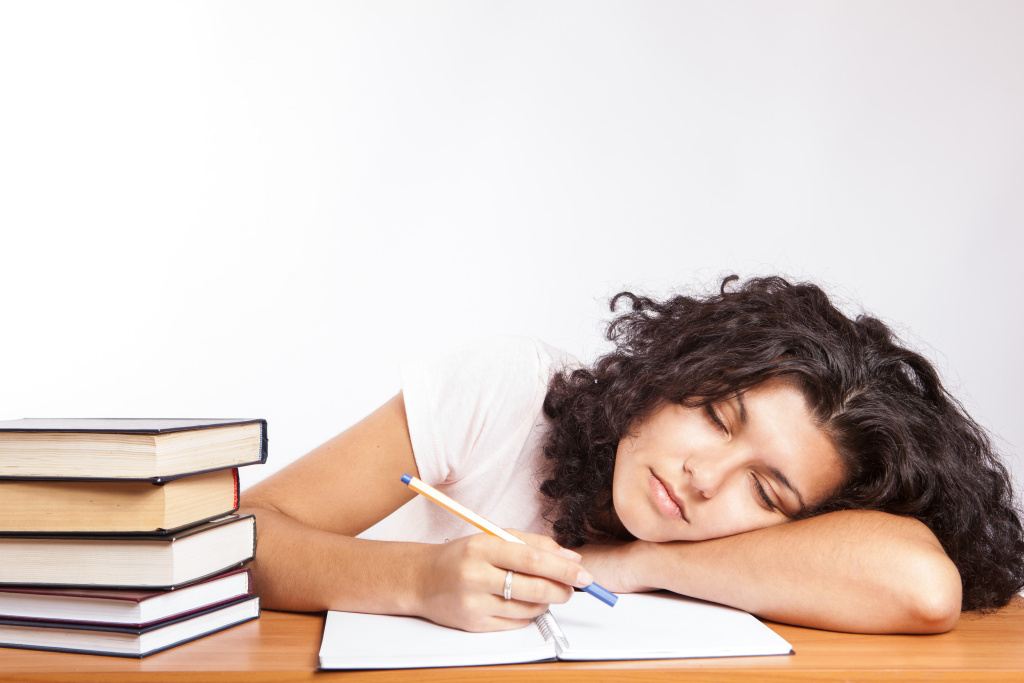 A girl fall asleep while working.