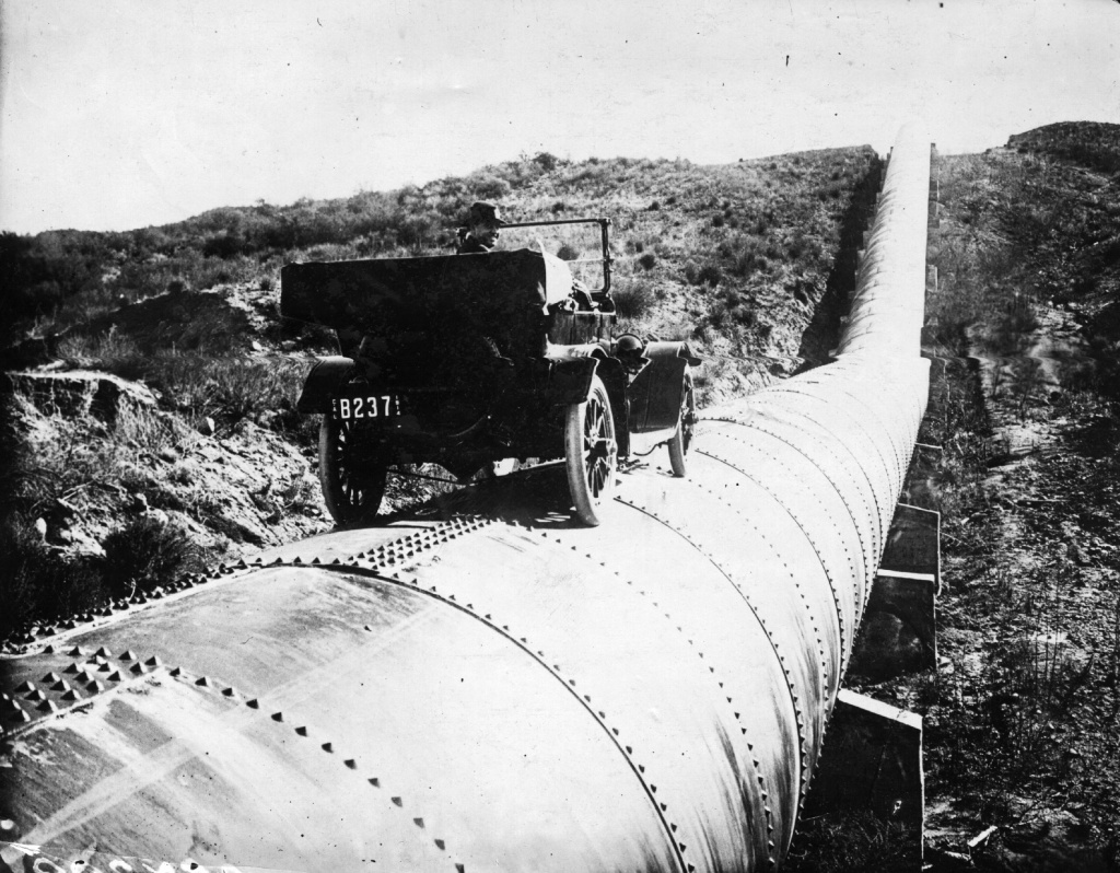 February 17, 1914: Mr. Bert Dingley drives a car along a section of the immense aqueduct of Los Angeles, California.