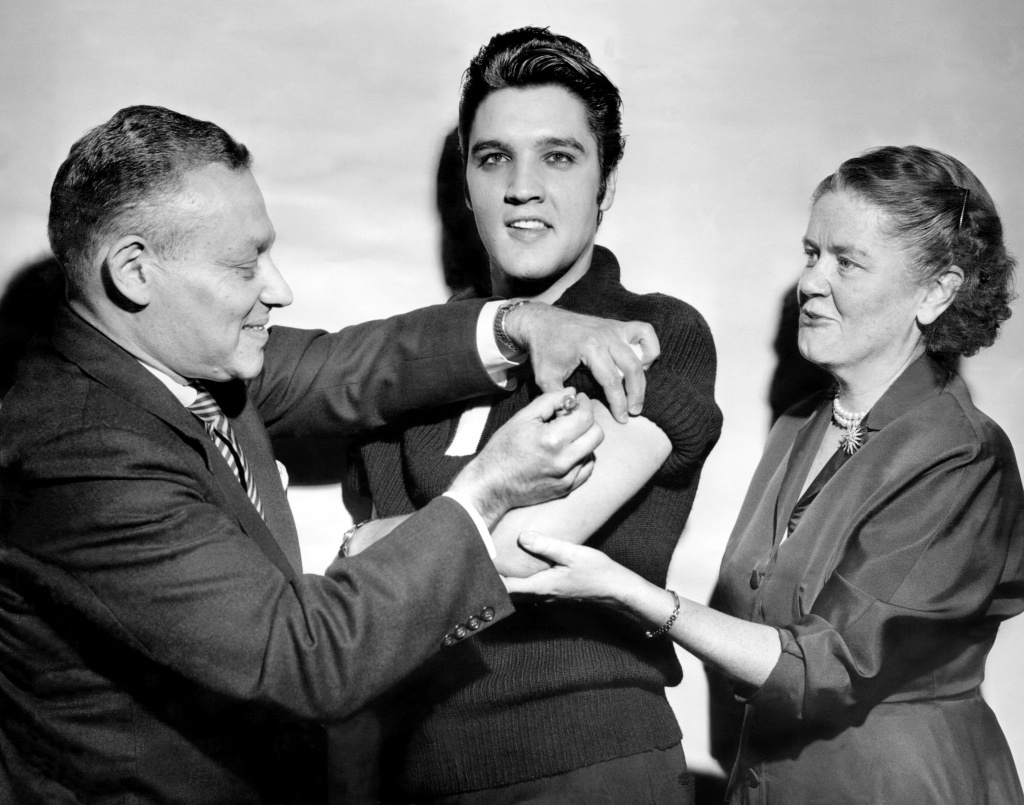 Elvis Presley got his polio vaccination from Dr. Harold Fuerst and Dr. Leona Baumgartner at CBS' Studio 50 in New York City on Oct. 28, 1956. The chart-topping singer took part in a March of Dimes campaign to convince teens to get vaccinated.