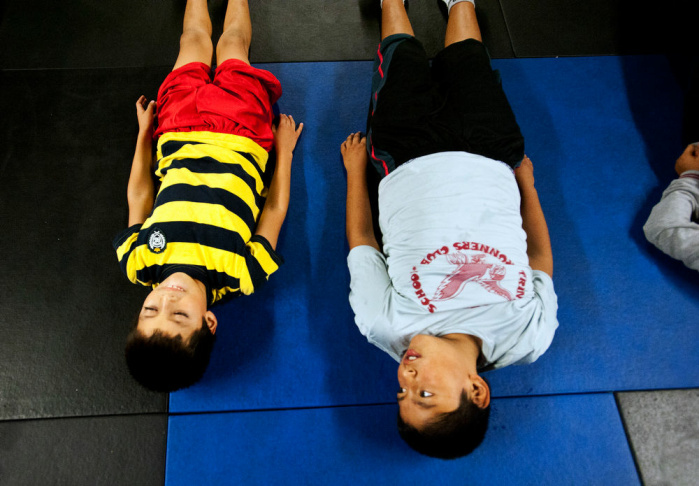 Seven-year-old Perla Bazaldua, left, stretches with PAL Fit coach Ronnie Teasdale during a CrossFit Tuesdays class on Dec. 11 in the underground parking garage at the Newton Police Station. The class is free for local kids, and is a part of the Police Activity League, a crime prevention program for community youth.