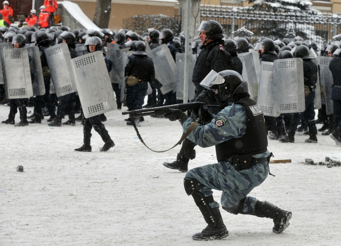 A riot policeman takes aim at demonstrators during clashes between protestors and police in the center of Kiev on January 22, 2014. At least two activists were shot dead today as Ukrainian police stormed protesters' barricades in Kiev, the first fatalities in two months of anti-government protests. Pitched battles raged in the centre of the Ukrainian capital as protesters hurled stones at police and the security forces responded with tear gas and rubber bullets.