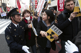 People confront police during an anti-war and anti-nuclear march Sunday, March 20, 2011, in Tokyo. Hundreds of protesters marched for peace and against nuclear power in Tokyo Sunday, as plant workers continue their race to avert disaster at the tsunami-damaged Fukushima Dai-ichi nuclear power plant in the north.