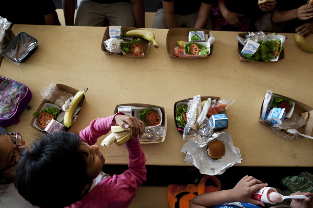 Students at Gratts Learning Academy for Young Scholars eat lunch, which includes a hamburger, banana, fruit and milk. LA Unified's