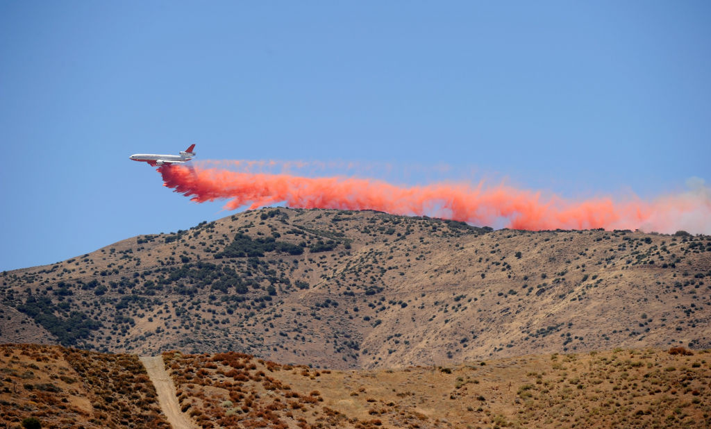 A firefighting DC-10 plane drops fire retardant on a ridge line to protect communication towers in Palmdale, California. The U.S. Forest Service is doubling the number of air tankers available to fight wildfires, but doing so could short-shift California's firefighting force.