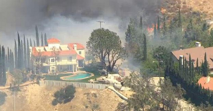 Heavy flames burn a hillside near a Granada Hills home with a swimming pool and tennis court where a line of firefighters spray water to protect it.