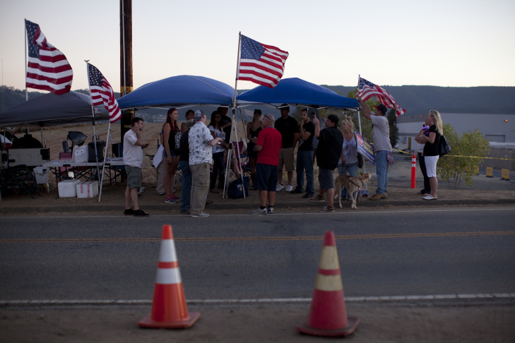 William Bello of Upland is draped in an American flag during a pro-immigration vigil in Murrieta. His family is originally from Mexico City and said that he supports the families coming to the states that are
