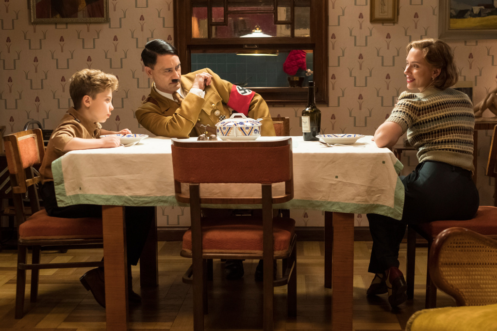 First still from the set of WW2 satire, JOJO RABIT. (From L-R): Jojo (Roman Griffin Davis) has dinner with his imaginary friend Adolf (Writer/Director Taika Waititi), and his mother, Rosie (Scarlet Johansson). Photo by Kimberley French. © 2018 Twentieth Century Fox Film Corporation All Rights Reserved