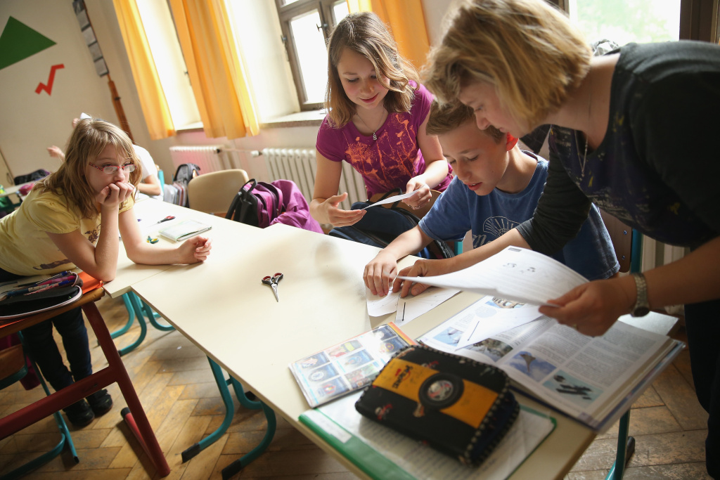 Volunteer teacher Andrea Urban, who is also the mother of two of her pupils, teaches a technology class as 6th graders Sarah Scheibe (L), Sophie Urban and Benno Bluhm look on at the Middle School.