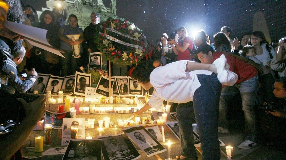 A woman lights a candle during a tribute to slain Mexican journalists at the Monument of Independence in Mexico City on May 5.