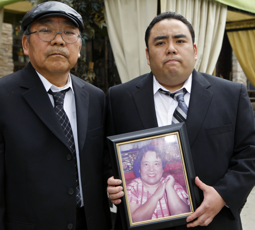 "This Thursday, Feb. 4, 2010 file photo shows Jeffrey Uno, right, and his father, Peter Uno, the son and husband of Noriko Uno, in framed photo, who died in an alleged ""sudden unintended acceleration"" crash in a Toyota Camry in August 2009, in Los Angeles. A jury on Thursday Oct. 10, 2013 found Toyota not liable for death of Noriko Uno."