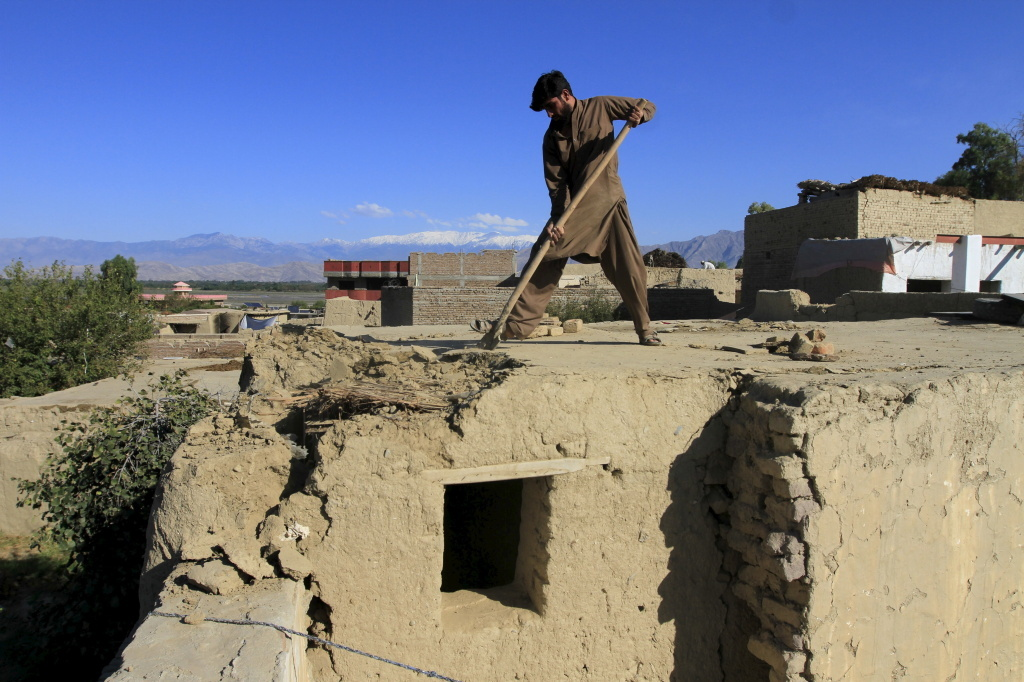 A man clears rubble from the roof of his house in the Behsud district of Jalalabad province, Afghanistan, on Tuesday.