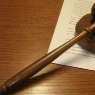 A wooden gavel rests on a short stack of legal papers.