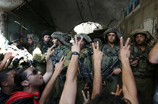 Israeli soldiers block foreigners, left wing Israelis and Palestinians as they protest against the Jewish settlement, close to an Israeli checkpoint located at the entrance of the West Bank city of Hebron, leading to the Jewish settlement of Beit Romano on July 3, 2010.