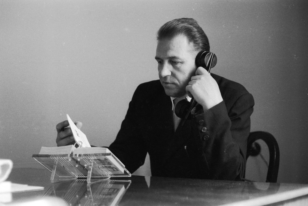 A man flips through his desk diary while talking on the telephone on May 18, 1961.
