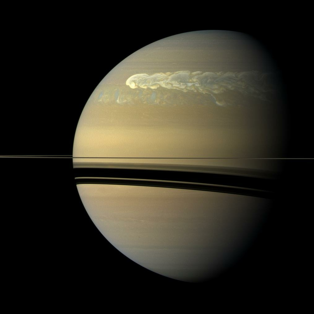 Side view of Saturn as a storm rages across its northern half.